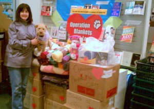 picture of Eileen Smulson with Ginger in a storage area of pet supplies.